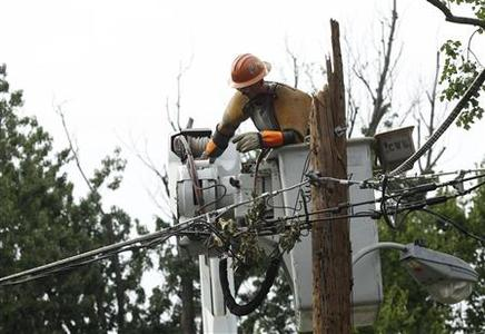 A Pepco contract worker works on a damaged utility pole in Silver Spring, Maryland, July 3, 2012. Nearly 1.4 million homes and businesses in the eastern United States remained without power amid a heat wave on Tuesday, and storm damage forced many Fourth of July celebrations to be canceled. Violent weekend storms and days of record heat have killed at least 22 people in the United States since Friday. Some died when trees fell on their homes and cars, and heat stroke killed others.REUTERS/Gary Cameron