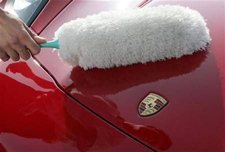 A member of staff cleans the front of a Porsche sports car with a duster, ahead of the Porsche Automobil Holding SE annual news conference in Stuttgart March 15, 2012. REUTERS/Alex Domanski/Files