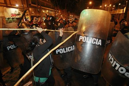 A woman clashes with police during demonstrations in solidarity with the protests against the Newmont Mining project in the region of Cajamarca, in downtown Lima July 4, 2012. A leader of protests against Newmont's $5 billion gold mine in Peru, known as Conga, said he was beaten by police on Wednesday - a day after three people died and 21 were injured in clashes between police and protesters. REUTERS/Enrique Castro-Mendivil