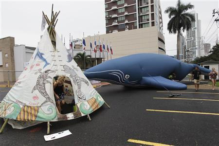 Protesters demonstrate next to an inflatable whale and a teepee with painted whales and dolphins outside the building where the International Whaling Commission (IWC) is being held during this week in Panama City July 4, 2012. Greenpeace, Surfers for Cetaceans and others organizations protested after the decision to create a whale sanctuary in the South Atlantic was rejected on Monday during the 64th annual meeting of the IWC, according to local and international media. REUTERS/Carlos Jasso