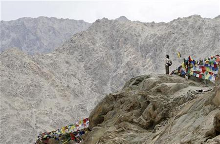 An Italian tourist stands on a hilltop overlooking Leh city from Namgyal Tsemo Gompa monastery in Leh, capital of Ladakh July 8, 2011. REUTERS/Fayaz Kabli/Files