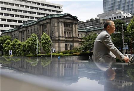 A man cycles past the Bank of Japan headquarters building in Tokyo June 14, 2012. REUTERS/Yuriko Nakao