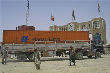 Men walk past a truck carrying supplies for NATO troops in Afghanistan, as it crosses into Afghanistan from the Pakistan border town of Chaman July 5, 2012. REUTERS/Saeed Ali Achakzai