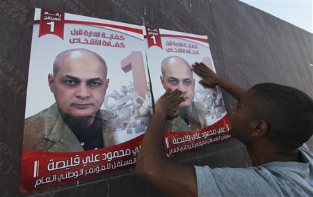 A man puts up a poster of Ali Kulaish, a candidate running for Libya's National Congress election in Benghazi July 4, 2012. REUTERS/Esam Al-Fetori