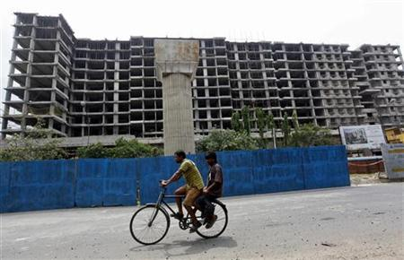 Men ride on a bicycle past a residential complex under construction in Kolkata May 31, 2012. REUTERS/Rupak De Chowdhuri/Files