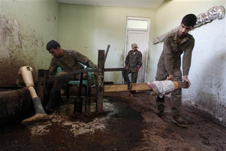 Afghan men work to make briquettes at the basement of NGO, the Kabul Orthopedic Organization (KOO) in Kabul July 4, 2012. REUTERS/Omar Sobhani