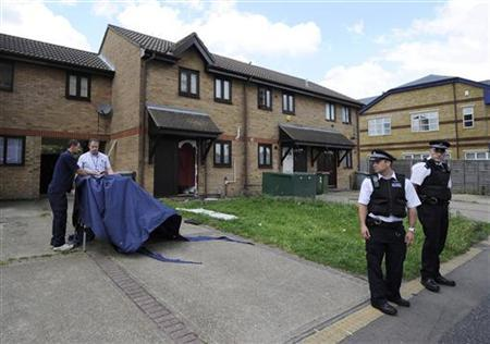 Police officers stand outside a house in Stratford east London, July 5, 2012.REUTERS/Paul Hackett