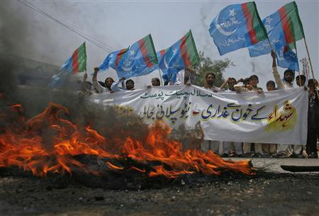 Supporters of Islami Jamiat Talaba, a student wing of Pakistan religious and political party Jamaat-e-Islami, hold their party flags as they burn tyres on the road during an anti-American demonstration in Peshawar, July 5, 2012. REUTERS/Khuram Parvez