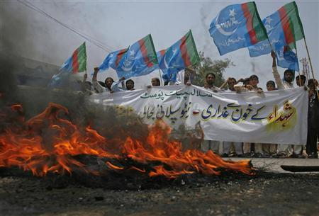 Supporters of Islami Jamiat Talaba, a student wing of Pakistan religious and political party Jamaat-e-Islami, hold their party flags as they burn tyres on the road during an anti-American demonstration in Peshawar, July 5, 2012. The banner reads in Urdu, ''Salala check post, Resumption of NATO supplies is a betrayal of the blood of martyrs''. REUTERS/Khuram Parvez
