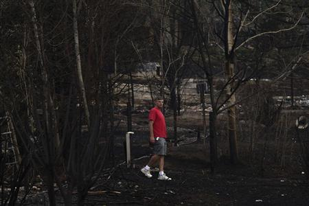 A man, who's house escaped fire damage, walks through his backyard after returning to his Mountain Shadows neighborhood which was devastated by the Waldo Canyon fire in Colorado Springs, Colorado on July 4, 2012. REUTERS/Adrees Latif