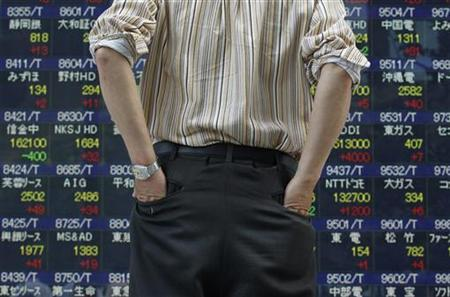A man looks at a stock quotation board outside a brokerage in Tokyo June 29, 2012. REUTERS/Yuriko Nakao/Files
