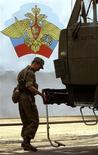 Российский военнослужащий осматривает грузовик около въезда на территорию военной базы в Душанбе, 17 сентября 2001 года. Россия нажимает на все рычаги давления, чтобы склонить Таджикистан к заключению договора о продлении присутствия в стратегически важной стране своей военной базы, сдвинув с мертвой точки переговоры, в затягивании которых Москва винит НАТО. REUTERS/Shamil Zhumatov