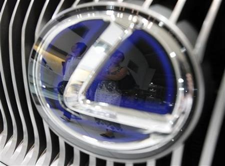 Visitors are reflected in a logo of a Toyota Motor's Lexus car at a showroom in Tokyo July 4, 2010. REUTERS/Issei Kato