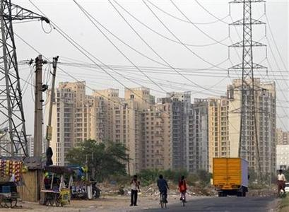 People ride their bicycles under overhead power cables, against the backdrop of multi-story residential apartments at Gurgaon, on the outskirts of New Delhi June 17, 2012. REUTERS/Ahmad Masood/Files