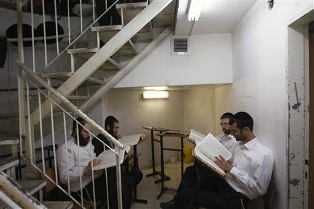 Ultra-Orthodox Jewish men study at Jerusalem's Mir Yeshiva, the largest Jewish seminary in Israel July 4, 2012. The ultra-Orthodox Jews have gone from being a tiny minority in Israel's mostly secular society to its fastest-growing sector, now about 10 percent of the 7.8 million population. They are exempt from military duty in Israel but draft deferments and state subsidies for the ultra-Orthodox have become a divisive political issue in Israel, where the government must decide a new law by August to ensure more of them do military service. Picture taken July 4, 2012. REUTERS/Ronen Zvulun