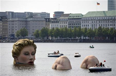 Boats gather around a sculpture of a mermaid at the 'Alster' lake in Hamburg in this August 3, 2011 file photo. REUTERS/Morris Mac Matzen