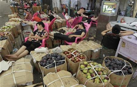 Vendors nap on chairs amongst boxes of fruits at a wholesale fruit and vegetable market in Wuhan, Hubei province July 6, 2012. REUTERS/Stringer