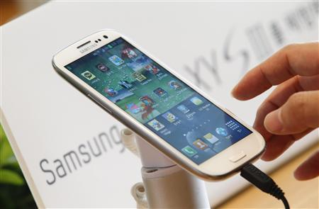 A man tries Samsung Electronics' new Galaxy S III smartphone that is on display at a store in Seoul in this June 26, 2012 file photo. REUTERS/Lee Jae-Won/Files