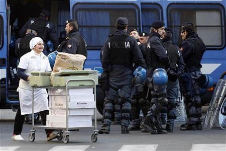 A worker carries food on a trolley past Italian police officers in downtown Rome December 14, 2010. REUTERS/Giampiero Sposito