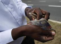 A man counts South African rand notes outside a stadium, June 15, 2010. REUTERS/Michael Buholzer