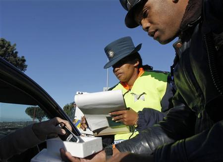 Police confiscate the mobile phone of a driver, caught using the device while driving, in Cape Town July 5, 2012. REUTERS/Mike Hutchings