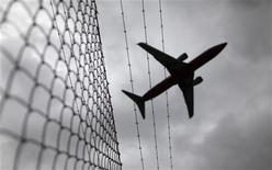 A passenger plane flies over a barbed wire fence as it approaches Sydney airport February 23, 2010. AREUTERS/Tim Wimborne