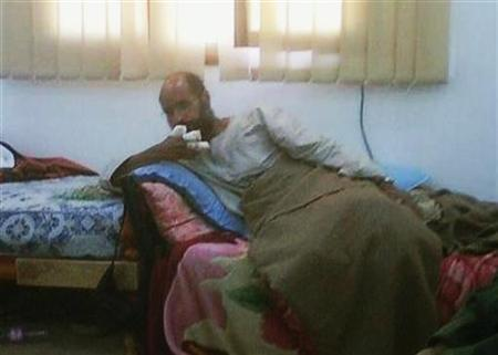 Saif al-Islam, son of the late former Libyan leader Muammar Gaddafi, sits after his capture, with his fingers wrapped in bandages and his legs covered with a blanket, at an undisclosed location, in this photograph aired on Free Libya TV on November 19, 2011. REUTERS/Libya Free TV via Reuters TV