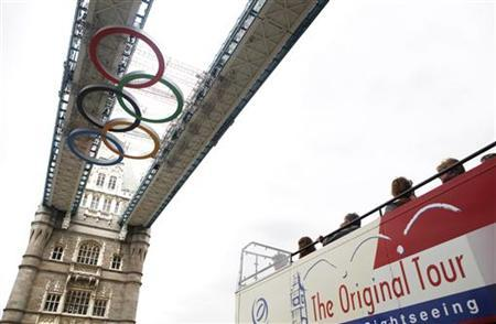 Passengers on a tour bus look up at the Olympic rings attached to the walkways over Tower Bridge in central London, June 26, 2012. REUTERS/Andrew Winning
