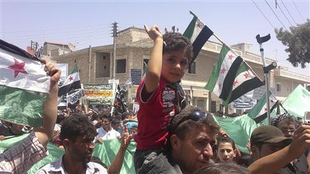 A boy joins demonstrators holding opposition flags as they protest against Syria's President Bashar al-Assad at Binsh near Idlib July 6, 2012. REUTERS/Shaam News Network/Handout