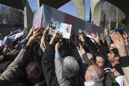 EDITORS' NOTE: Reuters and other foreign media are subject to Iranian restrictions on leaving the office to report, film or take pictures in Tehran. Iranian worshippers carry a picture and coffin of Iranian nuclear scientist Mostafa Ahmadi-Roshan, who was killed in a bomb blast in Tehran on January 11, during his funeral after Friday prayers in Tehran January 13, 2012. REUTERS/Morteza Nikoubazl