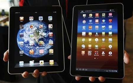 An employee of South Korean mobile carrier KT holds a Samsung Electronics' Galaxy tablet 10.1 (R) and Apple Inc's iPad at a registration desk at KT's headquarters in Seoul, in this August 10, 2011 file photo. REUTERS/Jo Yong-Hak/Files