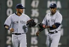 New York Yankees Darnell McDonald (L) and Curtis Granderson celebrate after beating the Boston Red Sox in their MLB American League baseball game at Fenway Park in Boston, Massachusetts July 6, 2012. REUTERS/Brian Snyder