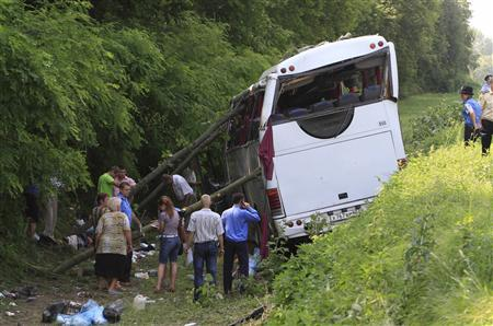 Ukrainian emergency services work at the site of a bus crash near the village Krasne, some 100km (62 miles) north of Kiev, July 7, 2012. REUTERS/Anatolii Stepanov