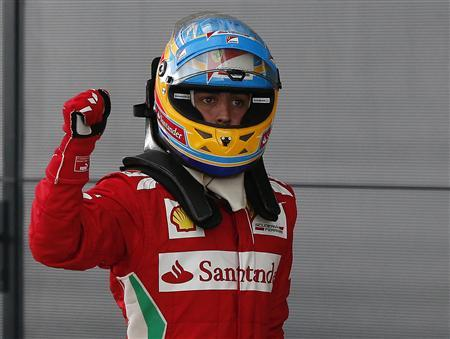 Ferrari Formula One driver Fernando Alonso of Spain gestures after taking pole position for the British F1 Grand Prix at Silverstone, central England, July 7, 2012. REUTERS/Phil Noble
