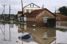 Машина лежит под водой в результате наводнений в селе Новоукраинское, близ Крымска, 7 июля 2012 года. Число жертв сильного наводнения в Краснодарском крае превысило сто человек, тысячи домов оказались затоплены после того, как на регион за несколько часов выпала двухмесячная норма осадков. REUTERS/VladimirAnosov