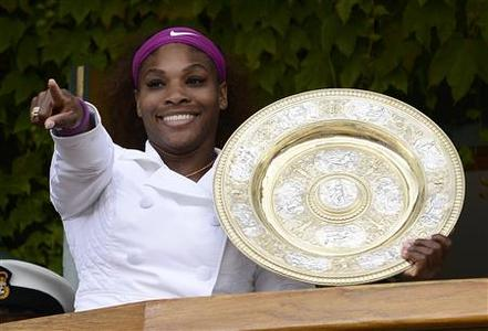 Serena Williams of the U.S. holds her trophy as she stands on the clubhouse balcony after defeating Agnieszka Radwanska of Poland in their women's final tennis match at the Wimbledon tennis championships in London July 7, 2012. REUTERS/Dylan Martinez