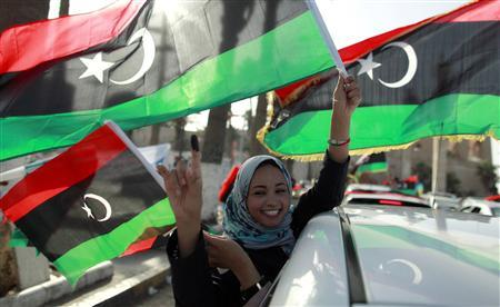 A woman celebrates with the new national flag on the streets after casting her vote during the National Assembly election in Tripoli's Martyrs square July 7, 2012. REUTERS/Zohra Bensemra