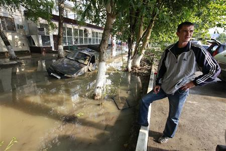 A local resident stands near a damaged car stuck in a flooded street in the town of Krymsk in Krasnodar region, southern Russia, July 8, 2012. REUTERS/Eduard Korniyenko