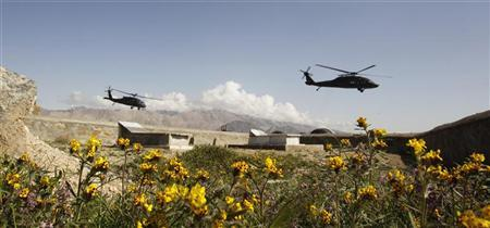 U.S. military Black Hawk helicopters fly past an Afghan graveyard in Forward Operating Base Methar Lam, in Laghman province, Afghanistan March 26, 2012. REUTERS/Erik De Castro