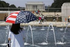 A tourist uses a patriotic umbrella to fight the punishing heat gripping the nation's capital at the National World War II Memorial in Washington July 6, 2012. REUTERS/Larry Downing