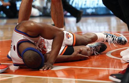 New York Knicks' Baron Davis grabs his right knee after suffering an injury while driving towards the basket in the third quarter of the Knicks' win over the Miami Heat, in Game 4 of their NBA Eastern Conference basketball playoff series in New York, May 6, 2012. REUTERS/Mike Segar