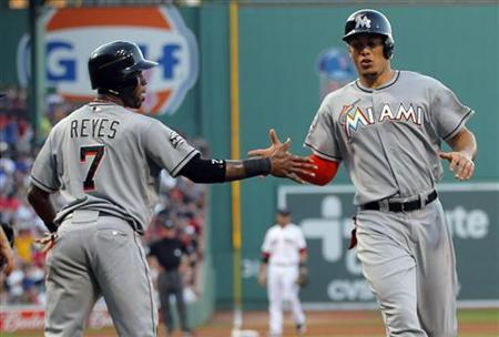 Miami Marlins Jose Reyes (L) and Giancarlo Stanton congratulate each other after scoring against the Boston Red Sox in the first inning of their MLB interleague baseball game at Fenway Park in Boston, Massachusetts June 21, 2012. REUTERS/Brian Snyder