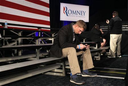 A supporter of Republican presidential candidate and former Massachusetts Governor Mitt Romney checks for news on his phone as he waits for the Romney rally to begin at his South Carolina Primary night rally in Columbia, South Carolina January 21, 2012. REUTERS/Brian Snyder