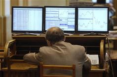 A trader sits in front of computer screens at the stock exchange in Madrid July 6, 2012. REUTERS/Andrea Comas