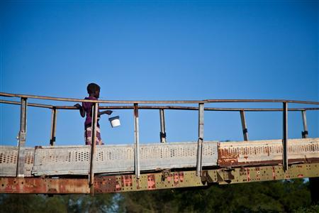 A girl walks across an old bridge after leaving the market in Pibor, South Sudan, June 24, 2012. REUTERS/Adriane Ohanesian