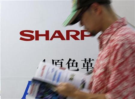 A man walks past Sharp Corp's advertisement board at an electronics store in Tokyo June 8, 2012. REUTERS/Toru Hanai