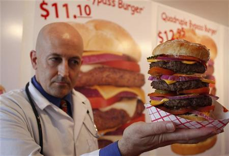 Heart Attack Grill owner Jon poses with a quadruple bypass cheese burger in Chandler, Arizona June 17, 2009. REUTERS/Joshua Lott