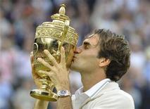 """Швейцарец Роджер Федерер целует кубок, завоеванный на турнире """"Уимблдон"""" в Лондоне, 8 июля 2012 года. Триумфатор завершившегося в воскресенье Уимблдона, швейцарец Роджер Федерер впервые за последние два года возглавил рейтинг сильнейших теннисистов мира по версии ATP. REUTERS/Toby Melville"""