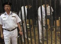 A policeman stands guard while Gamal (C) and Alaa Mubarak (R), sons of former President Hosni Mubarak prepare to sit in a court room cage in Cairo, July 9, 2012. REUTERS/Stringer