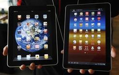 """Samsung Electronics ha derrotado a Apple en la última batalla de la guerra de patentes que mantienen ambas compañías cuando un juez británico dictaminó que las tabletas Galaxy de Samsung no infringen los diseños del iPad de la firma estadounidense porque no son """"tan guay"""". En la imagen de archivo, un empleado del minorista surcoreano KT sostiene la tableta Galaxy tablet 10.1 de Samsung Electronics (derecha) y el iPad de Apple en la sede de la empresa en Seul, el 10 de agosto de 2011. REUTERS/Jo Yong-Hak/Files"""